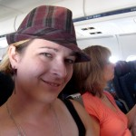 Erin in a purple fedora, on a plane, her mom in the background.