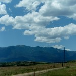 A dirt road runs from the bottom of the image off to the right side, and fluffy white clouds float over a distant mountain.