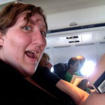 Lissa with a silly smile, on the plane, book in hand.